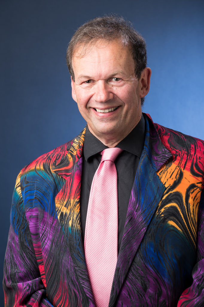 Port Phillip Mayor Cr Dick Gross wearing a multi-coloured jacket and pink tie with a contrasting black shirt.